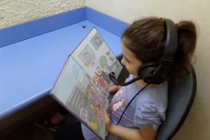 ילדה קוראת ספר עם אוזניות
